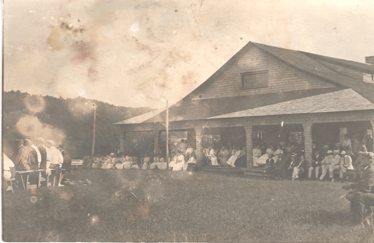 Early photo of the Quaker Lake Cottagers Association Clubhouse. It's hard to tell for sure, but I'm guessing that they are viewing a baseball game, with those sitting on the left of the picture being the players. It looks as if there are baseballs on the ground behind them.