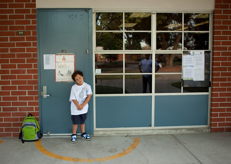 Marlin standing in front of his first grade class room.