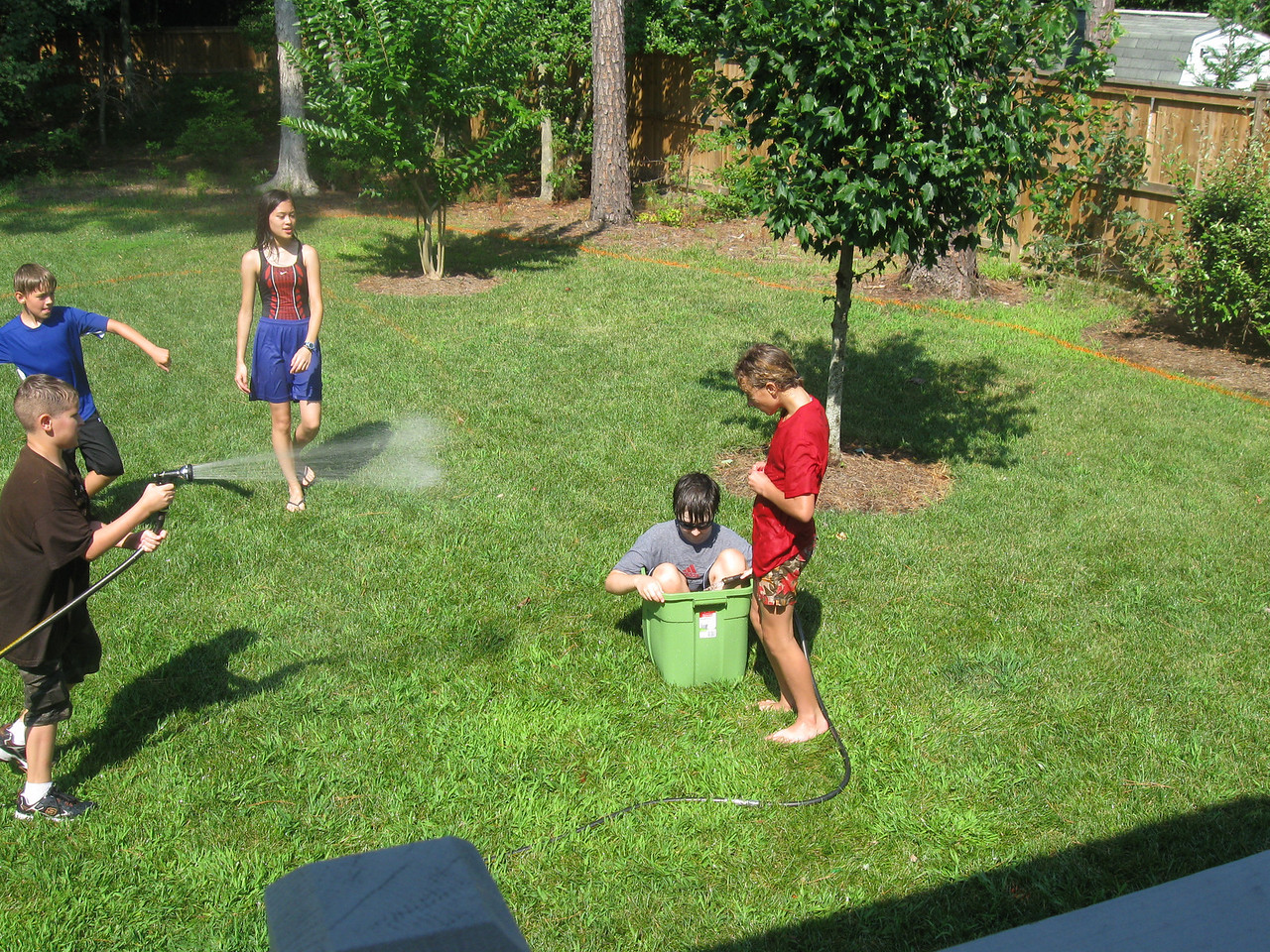 Josh sprays Matt (in tub) while Landry looks on.  Zach is launching a water balloon at Matt while Mandy looks on.