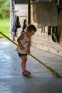 Horses are messy so Kenzie helps sweep up the barn.