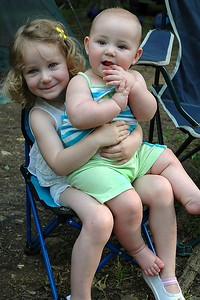 Mary holds Lily on her lap.  Mary only weighs 5 pounds more than Lily.