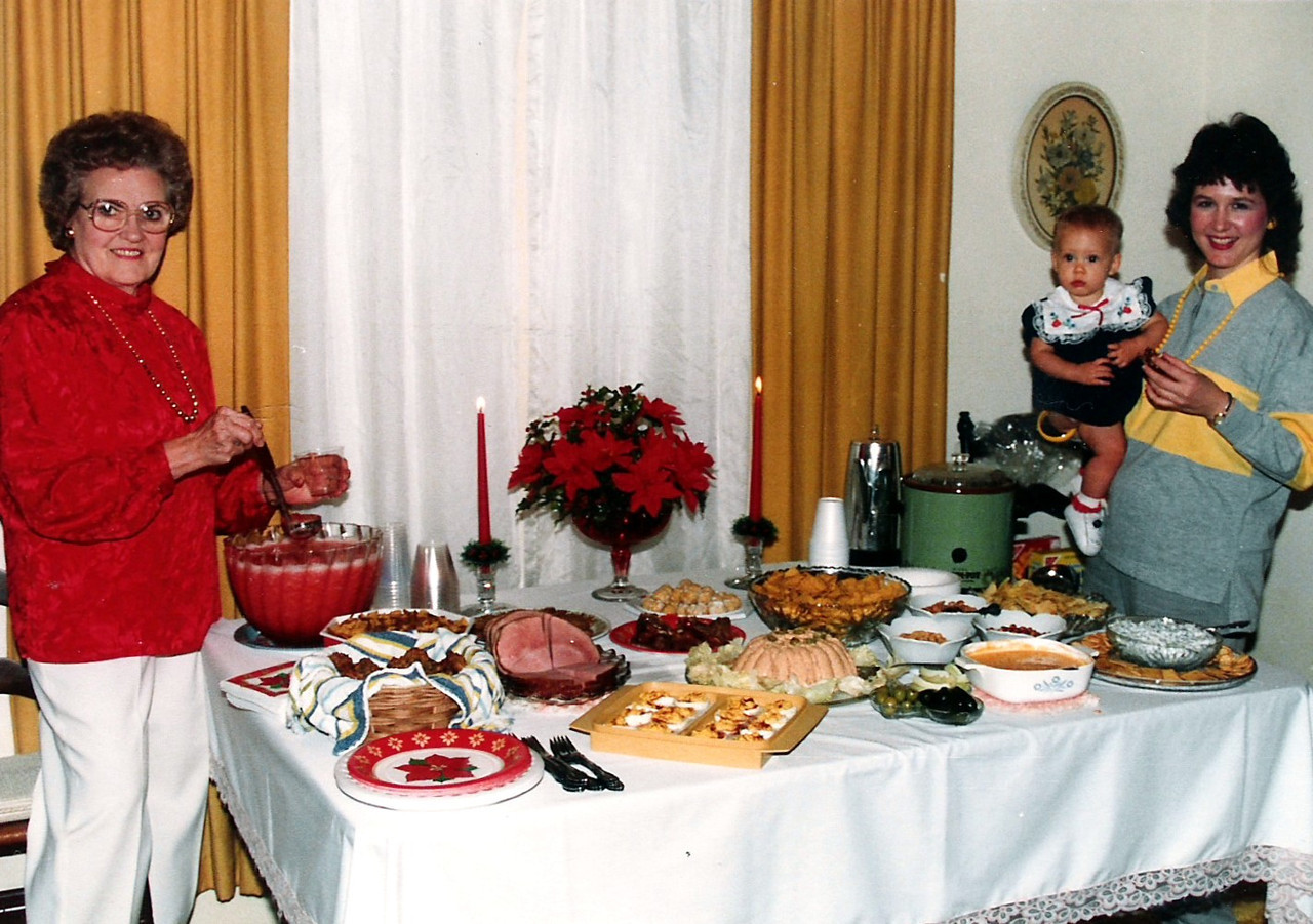 Grandma stands by big Christmas feed.  Mary Jane and Sarah Jane look on.  No one could throw a party like grandma could.