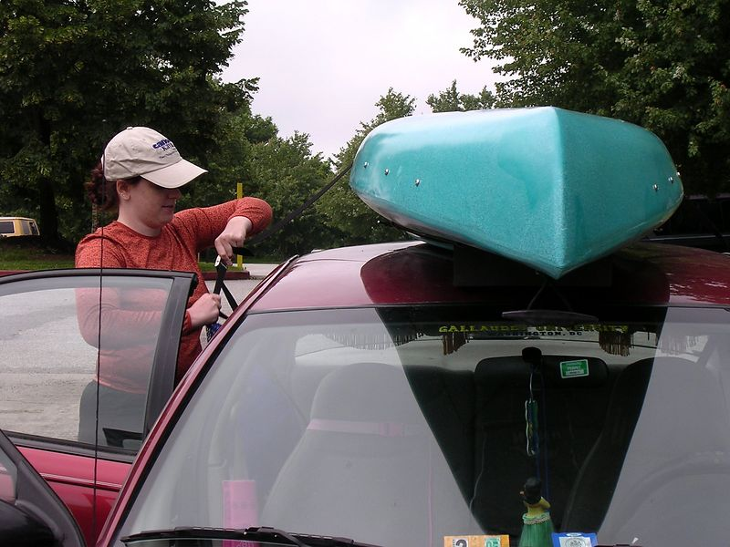 Undoing the very long cam straps that keep the kayak firmly in place while the car is moving.