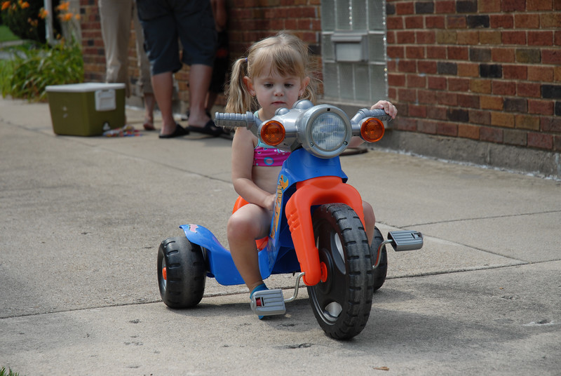 My most adorable niece Katie at my dad and sister's July birthday party.  Ryan has outgrown his big wheel and found it is just right for his cousin.  She is checkin' it out before taking it for a spin.