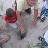 Grandfather helps lift the treasure from its hole.