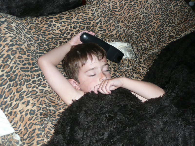 My son... asleep in my bed with the remote in hand...