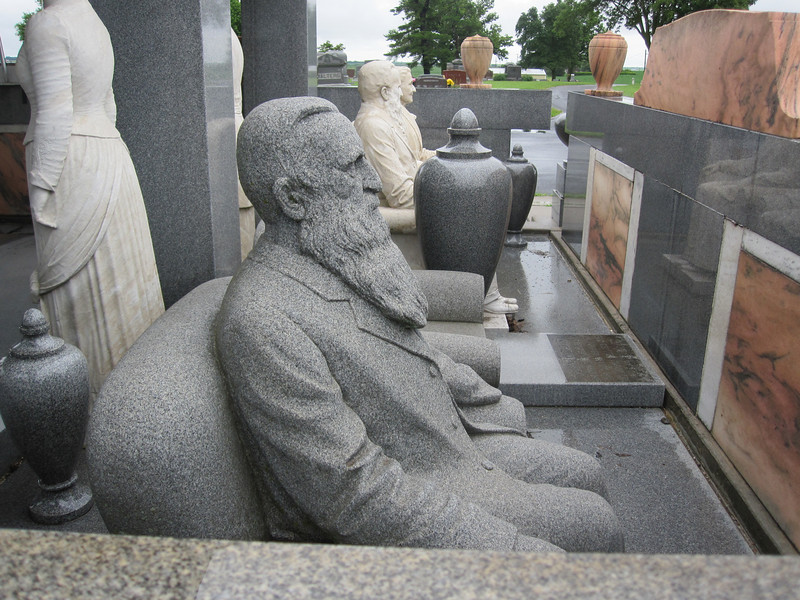 "This granite sculpture shows Davis as an old man.  The ""chair"" next to him is vacant.  You can see that his left sleeve is empty.  He lost a hand due to an infection."