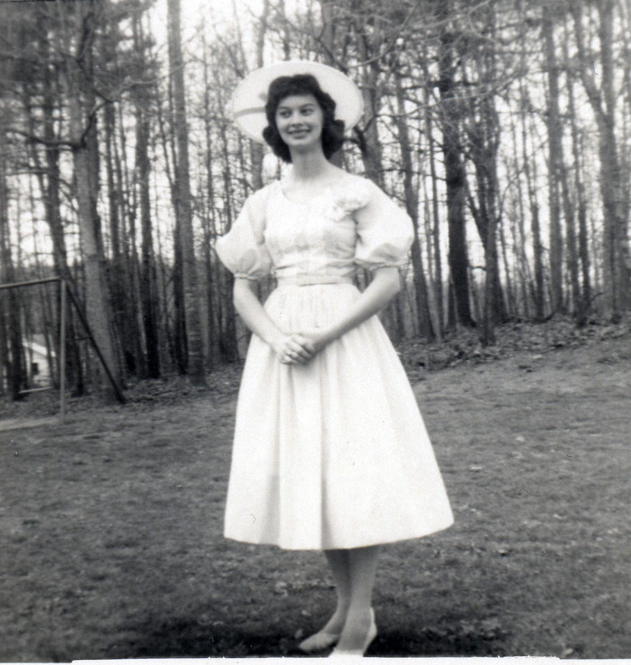 Mary Carolyn Mitchell at Easter in front yard at Mitchell home. Gibson House in background. Circa 1960. Dress was light green - white hat.