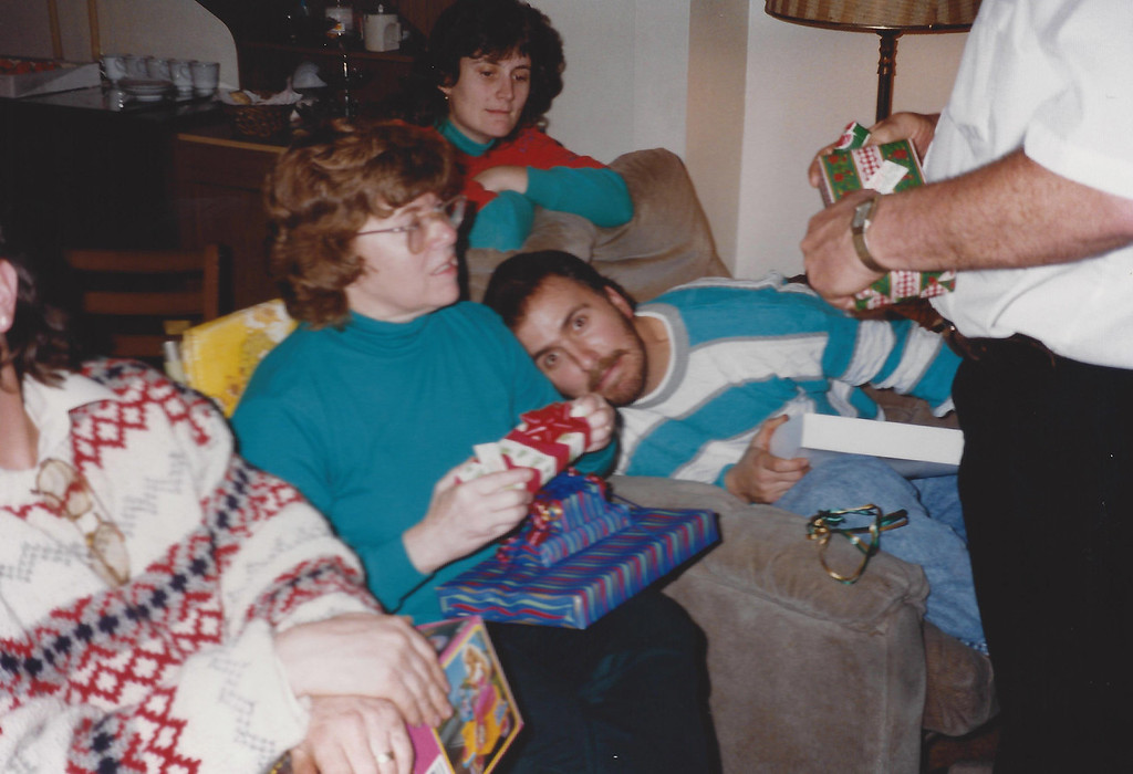 Mom unwrapping a Christmas gift and Mike just being Mike