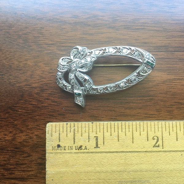 10. Oval bow pin with 31 diamonds, 2 emeralds