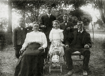 DEE MOORE FAMILY PORTRAIT Photo taken in 1905  A less formal but at least complete photo of the Dee Moore family. I love that Lizzie has her doll and stroller in the photo.  L to R: Dee Jr, Lizzie (wife), William, Lizzie (daughter), Milton, and Dee Moore Sr  Historical note: According to The History of Gonzales Co., Texas, page 150, Dee Moore was the first postmaster for the Maurin Community Post Office. The application for the Post Office was submitted March 28, 1900 and approved July 3, 1900. He served in this capacity for two years.   From the Texas State Historical Society page: The Gonzales County community of Maurin, named for a French stonemason who lived in the settlement, was probably established in 1889 as a station on the San Antonio and Aransas Pass Railway halfway between Gonzales and Dilworth. The village acquired a post office in 1900, but it closed in 1915. The year before, an F. Maurin, Jr., was the postmaster and also operated a general store. By 1915 Maurin had a general store, a telephone connection, and a population of twenty. In 1931 it had two businesses in addition to the rail station. In 1932 the railroad was abandoned. That year Maurin listed forty inhabitants. That figure remained constant until 1948, although by 1945 one of the businesses had closed. By 1949 population figures had become unavailable, and in 1965 Maurin was no longer identified on county highway maps.