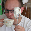 Mike sips tea while holding the beater dripping with real whipped cream.