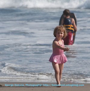 This little girl looks adorable in her cute swim suit, but those hands are full of sand she's been throwing at her brother in the background.