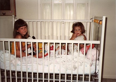 Catherine 3, and Lauren 2, play in Granny's baby bed     1982