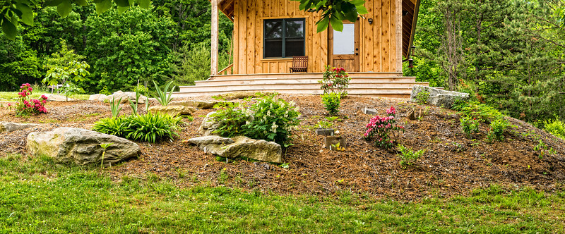 Front of the cabin with spring blooms ... the large bushes are native Mountain Laurel.