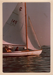 "Nick waving from his Town Class sloop ""Pal"" with  cousin David Brewster as crew.  Marblehead, 1974."