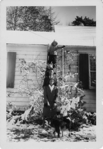 Nichols family posing (for possible Christmas card?) on the long ladder sometimes used to clear snow from the roof.