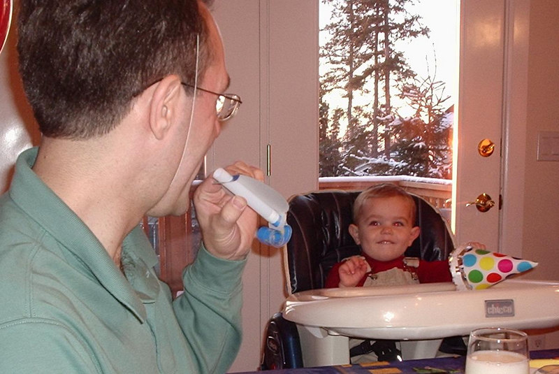 Dad demonstrates how to blow a party favor.