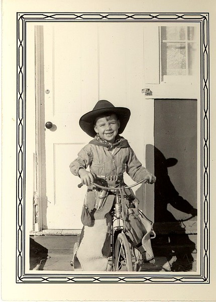 Donald Hill in cowboy outfit riding a tricycle.