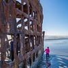 Girl explores shipwreck on the beach at Fort Stevens, Warrenton, OR