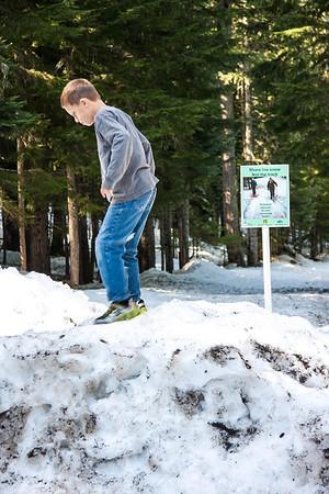 Grant climbs a tall snow bank.