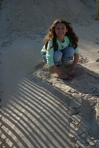 Anisa warming her feet in the sand.