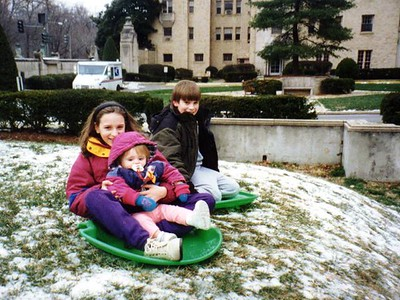 Sydney Jean Kane getting a sled ride from Jessica in front of the Kennedy-Warren with Ryan looking on.