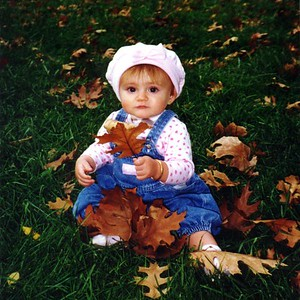 Sydney Jean Kane enjoying the fallen leaves in Constitution Gardens.   An East Coast Autumn. Sydney's first Halloween was celebrated at a wonderful Kennedy-Warren party. They say it is often prettier (not much rain this year), but we weren't disappointed with the different colors of the leaves in Shenandoah National Park. We also found time to explore Luray Caverns. Veterans' Day and the following weekend was enjoyed in New York City. (30 Oct - 22 Dec 1998)
