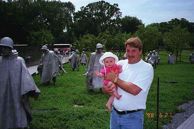 Uncle Andrew and Sydney Kane in front of the Korean War Veterans Memorial.   The memorial was dedicated July 27, 1995, the 42nd anniversary of the signing of the Korean War armistice. The design includes 19 sculptures of soldiers arrayed before a black granite wall etched with images taken from wartime photos. The American flag flies at the apex of the memorial near a circular reflecting pool.
