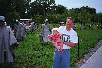 Pat and Sydney Kane in front of the Korean War Veterans Memorial.   The memorial was dedicated July 27, 1995, the 42nd anniversary of the signing of the Korean War armistice. The design includes 19 sculptures of soldiers arrayed before a black granite wall etched with images taken from wartime photos. The American flag flies at the apex of the memorial near a circular reflecting pool.