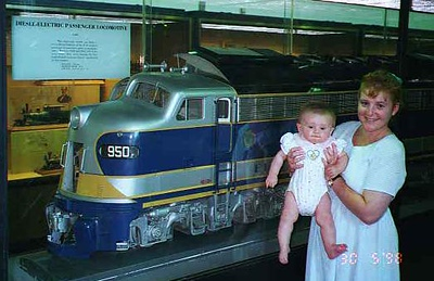 Kathy and Sydney in front of a model of a diesel-electric passenger locomotive at the National Museum of American History.