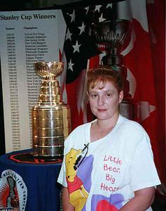 Kathy Kane in front of the National Hockey League's Stanley Cup on display at Union Station. The bowl that currently sits atop the Stanley Cup is a carefully constructed copy of the original bowl purchased by Lord Stanley in 1893. The original trophy was retired in 1969 because it had become brittle and easily damaged. It can still be viewed at the Hockey Hall of Fame in Toronto.