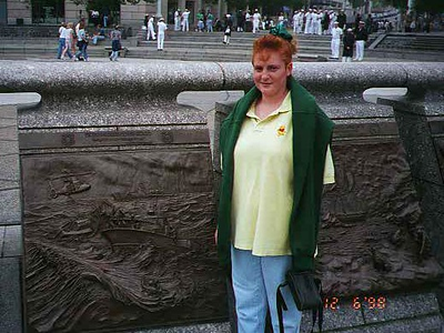 Kathy standing in front of a plaque at the U. S. Navy Memorial.