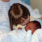 Sydney Jean (2 yrs) giving kisses to baby brother, Christopher Ross Kane (born 25 Jan 2000), at Community Memorial Hospital, Ventura CA. 27 Jan 2000.