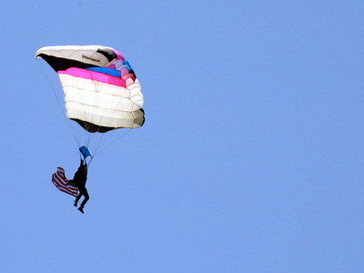 A parachutist is carrying in the American Flag to kick-off the Seabee Days festival