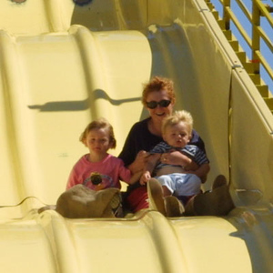Kathy is taking Sydney and Christopher down the Super Slide at the Seabee Days festival