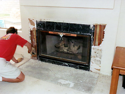Preparing the fireplace for new doors, tile and a mantel. The old fireplace had a white tile hearth and surround as well as a small drywall bumpout for the mantel.