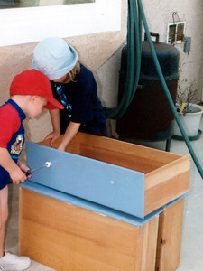 So that we can paint her dresser, Sydney is getting Christopher to help her remove the drawer knobs. This is one of the dressers that my brother, Andrew, and I had growing up (the other is in Christopher's room)!