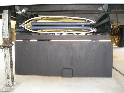 To transport our 10-ft Porta-Bote, I built an inexpensive undercarriage storage unit for our 5th wheel trailer. I used two 12-ft galvanized roofing panels to protect the boat from road debris. The panels are supported at the front and in the middle by angle irons (bent into a U-shape and bolted to the frame) and at the rear by the axle. A hinged plywood door covers the front opening.