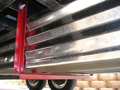 To transport our 10-ft Porta-Bote, I built an inexpensive undercarriage storage unit for our 5th wheel trailer. I used two 12-ft galvanized roofing panels to protect the boat from road debris. The panels are supported at the front and in the middle (shown) by angle irons (bent into a U-shape and bolted to the frame) and at the rear by the axle. A hinged plywood door covers the front opening.