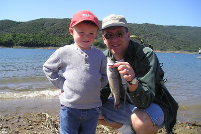 """Christopher and Pat Kane with the trout Christopher caught in the stocked pool during the kids' fishing day at Lake Casitas. Christopher didn't want to """"catch and release"""" and the fish wasn't in much shape to swim away anyway, so the neighbor got to eat it."""