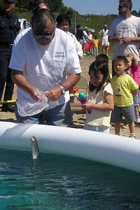 Sierra Moore just reeled in a trout from the stocked pool during the kids' fishing day at Lake Casitas. Her brother, Eli (in yellow shirt), is watching and patiently waiting for his turn.