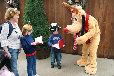 Christopher getting Pluto to sign his book as Kathy and Sydney look on.