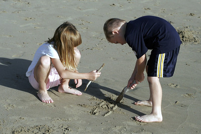 Sydney & Christopher playing tic-tac-toe in the sand at the beach.