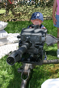 Christopher ready to shoot a crew-served weapon during Seabee Days
