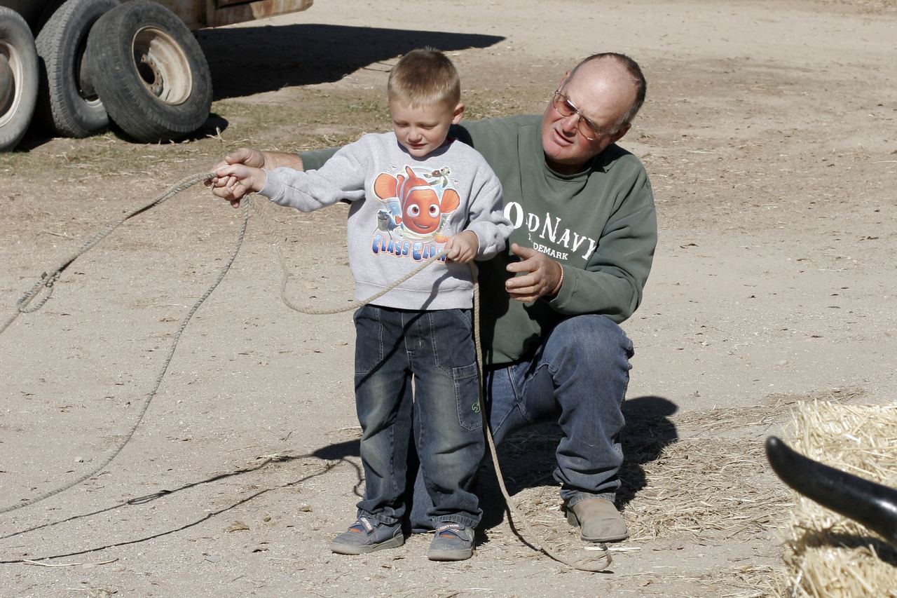 Uncle Frank giving Christopher lessons on how to rope a steer.