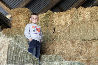 Christopher on a haystack in Uncle Frank's barn.