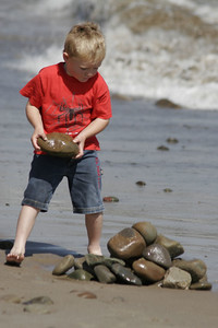 Christopher is building a rock pile at the beach.
