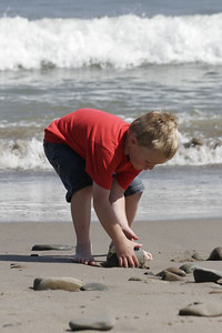 Christopher is finding rocks to build a rock pile at the beach.