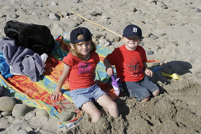 Sydney and Christopher are burying themselves in the sand at the beach.